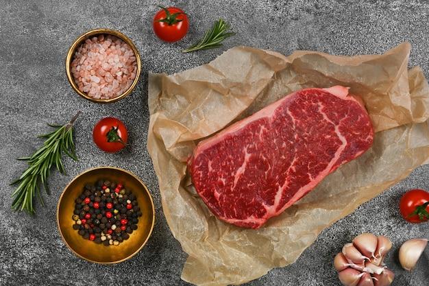 갈색 종이 양피지 포장에 마블링된 생 등심 쇠고기 스테이크 한 개를 테이블에 향신료와 함께 닫습니다