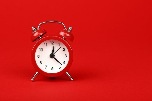 赤い背景の上の1つの赤い目覚まし時計を閉じる