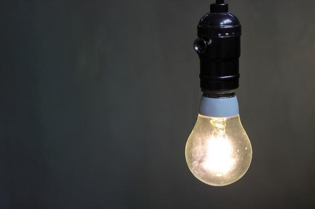 コピースペース、黒背景で装飾的な電球と1つのレトロ光ランプを閉じます。