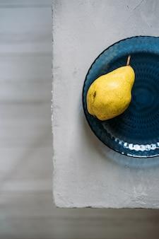 회색 배경의 파란색 유리 접시에 익은 노란색 배 한 개를 닫습니다.