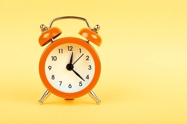 Закройте один маленький оранжевый металлический двойной колокол ретро-будильник на пастельно-желтом бумажном фоне с копией пространства, вид спереди под низким углом