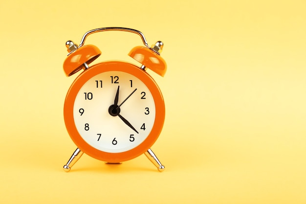 Close up one small orange metal twin bell retro alarm clock over pastel yellow paper background with copy space, low angle front view