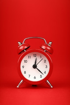 Close up one small red metal twin bell retro alarm clock over red paper background with copy space, low angle front view