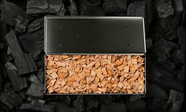 真上にある黒い塊の木炭片に広葉樹のハンノキチップを入れたステンレス鋼の金属製スモーカーボックスをクローズアップ