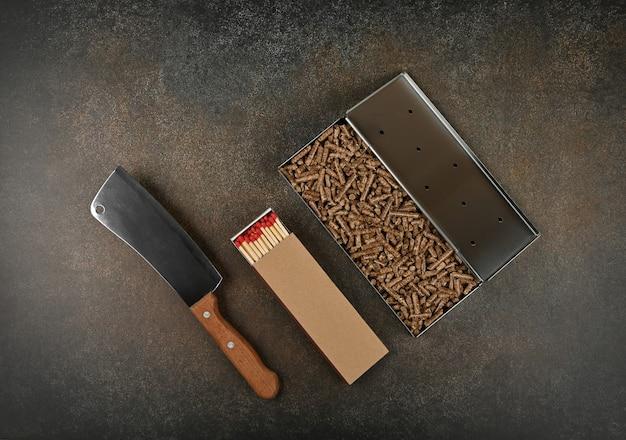 Закройте одну металлическую коптильную коробку из нержавеющей стали с гранулами из твердых пород древесины, спичками для гриля и ножом для мяса на столе, вид сверху, прямо над