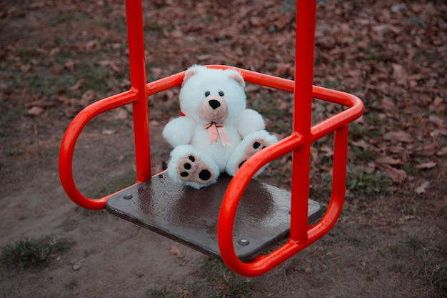 Close-up one teddy bear is sitting on a children's swing in red