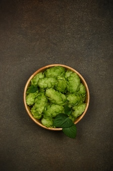 Close up one wooden bowl of fresh green hop flowers on dark grunge brown table background, elevated top view, directly above