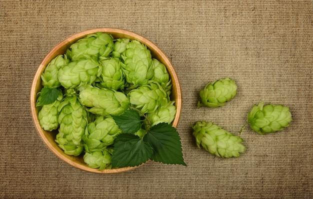 Закройте одну деревянную миску со свежими зелеными цветами хмеля на фоне коричневого джутового холста, вид сверху, прямо над