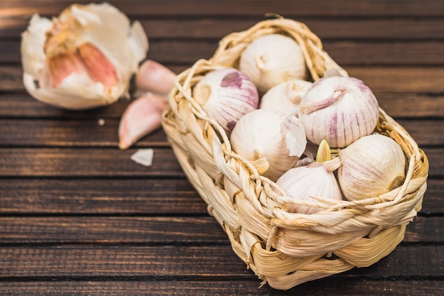 Close-up of onions in basket near garlic cloves on wooden plank