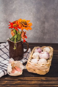 Close-up of onions; garlic cloves; flower and cloth on wooden tabletop