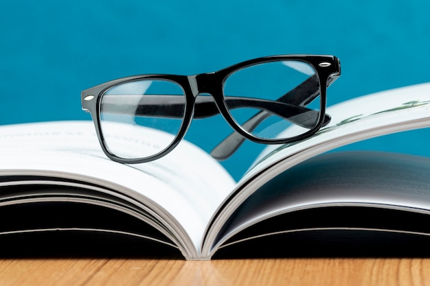 Close-up open book with glasses