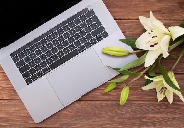 古い木製の机の上に花と開いているラップトップを閉じます。フラットレイスタイル
