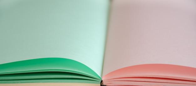 クローズアップ、メモ帳のページを開く、繊細なポストカード、パステルカラー。テキスト用のスペース。空白の色のページで本を開きます。セレクティブフォーカス