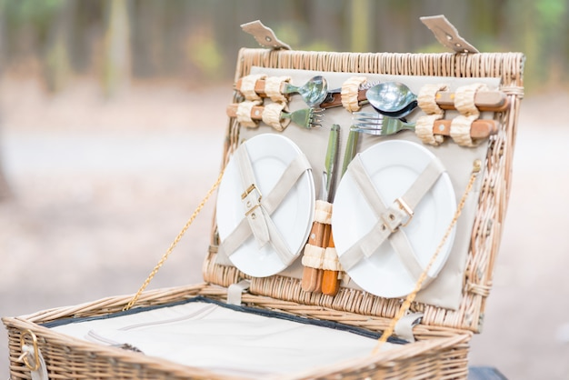 Close up of an open picnic basket over wooden table in the park.