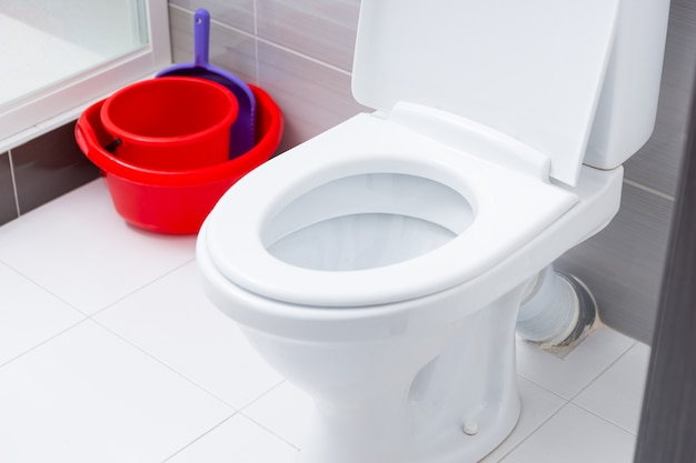 Close up on open toilet in bathroom with white and gray tiles next to red cleaning buckets and dust pan