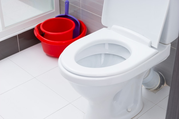 Close up on open toilet in clean bathroom with white and gray tiles next to red cleaning buckets and dust pan