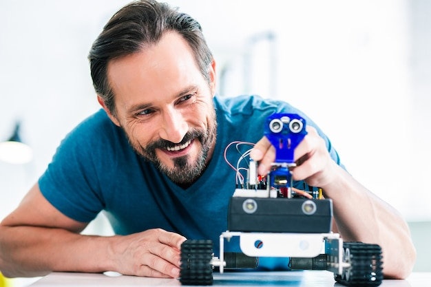 Close up of an optimistic delighted bearded man using his robotic device while enjoying his hobby