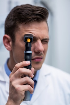 Close-up of optometrist looking through ophthalmoscope