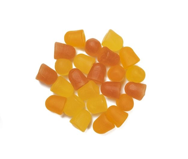 白い背景の上のクローズアップオレンジと黄色のマルチビタミングミ。健康的なライフスタイルのコンセプト。