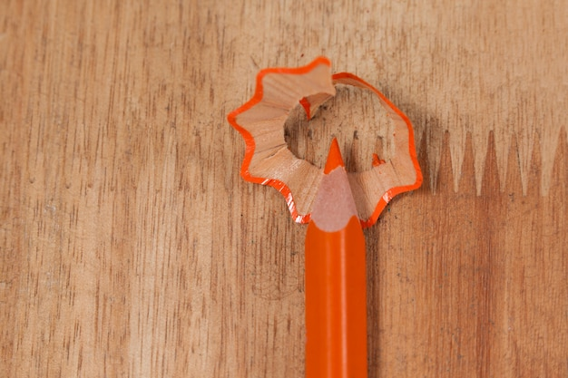 Close-up of orange colored pencil with shavings