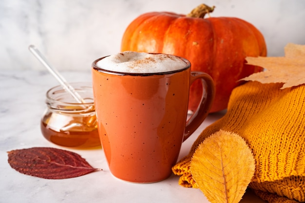 Close up of orange cup with coffee or pumpkin spice latte, autumn leaves, pumpkin, and honey jar on white surface