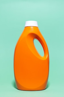 Close-up of orange detergent bottle on wall of aqua menthe color.