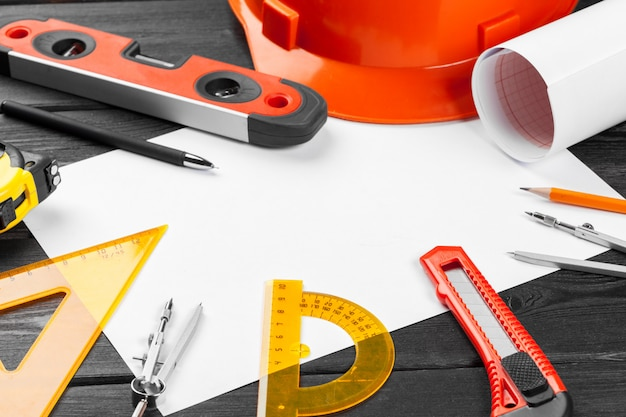Close up orange hardhat and variety of repair tools with copyspace in the middle over wooden