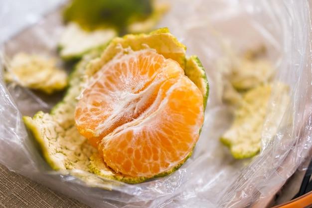 Крупный план, оранжевый очищенный на полиэтиленовом пакете