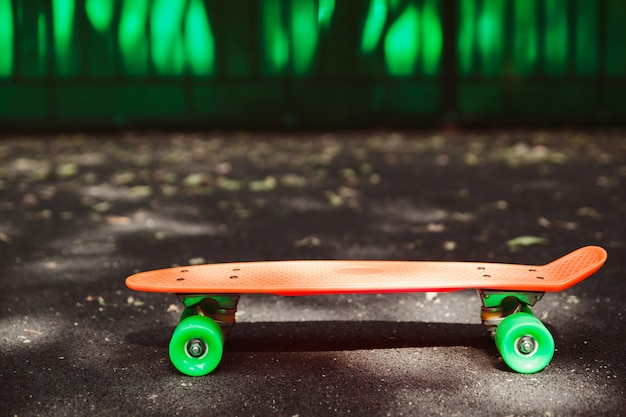 緑の壁の後ろにアスファルトの上のオレンジペニースケートボードを閉じる