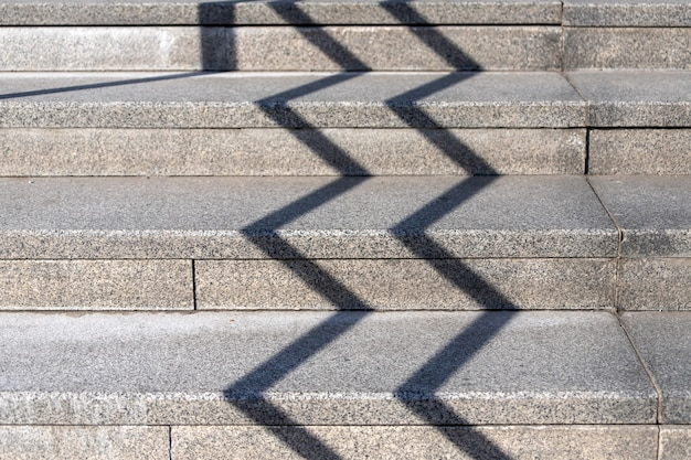 Close-up of ordinary stone simple stairs made of concrete and cement with geometric shadow