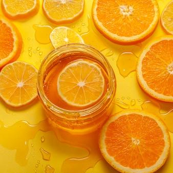 Close-up organic honey and orange slices