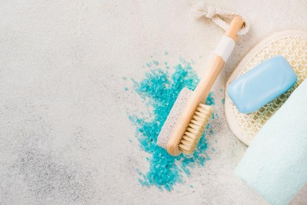 Крупным планом органическая соль и спа-щетка с полотенцем