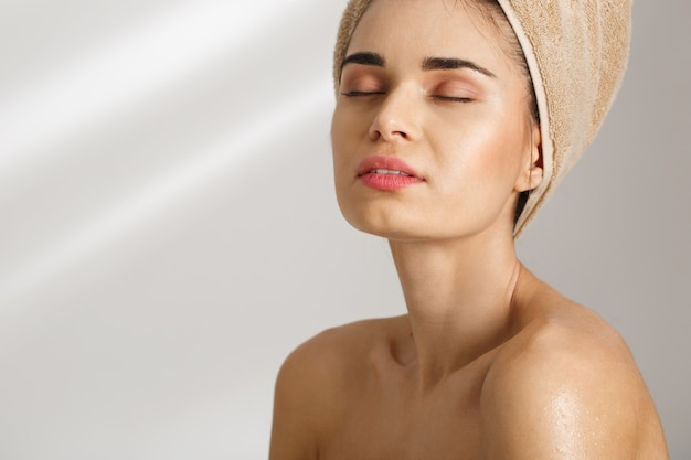 Ortrait крупного плана красивой шикарной молодой женщины после ванны стоя покрыто в полотенце с закрытыми глазами