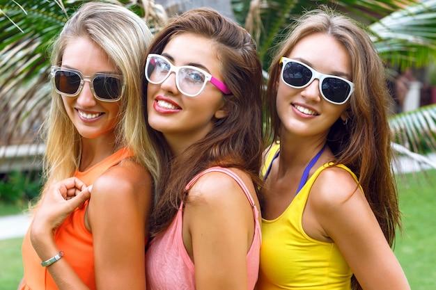 밝은 여름 드레스와 선글라스를 착용하는 세 젊은 예쁜 여자의 야외 패션 밝은 라이프 스타일 초상화를 닫습니다. 웃는 끝은 휴가를 즐기십시오.
