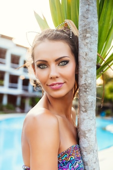 Close up outdoor fashion portrait of beautiful tanned woman with stylish bright smoky eyes look, bright colorful dress, and diamond wreath, posing near poll at summertime.