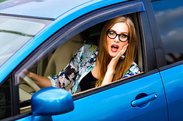 Close up outdoor lifestyle travel photo of young blonde hipster  woman driving car, glasses and bright clothes, big smile happy mood, enjoy her nice day, young businesswoman .