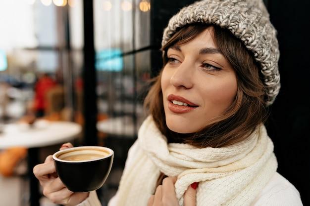 Chiuda sulla foto all'aperto della donna affascinante europea che indossa berretto lavorato a maglia e sciarpa che beve caffè sul caffè della città con l'atmosfera natalizia delle luci
