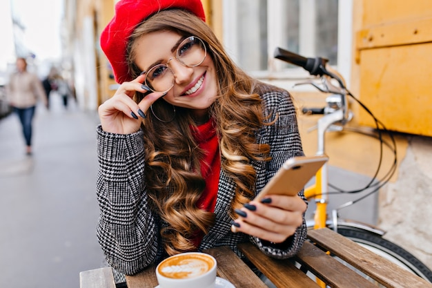 Close-up outdoor photo of lovely female model in glasses drinking hot cappuccino on urban background