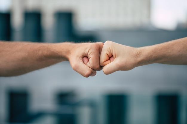 一緒に保持している2人の男性の拳の屋外写真を閉じる