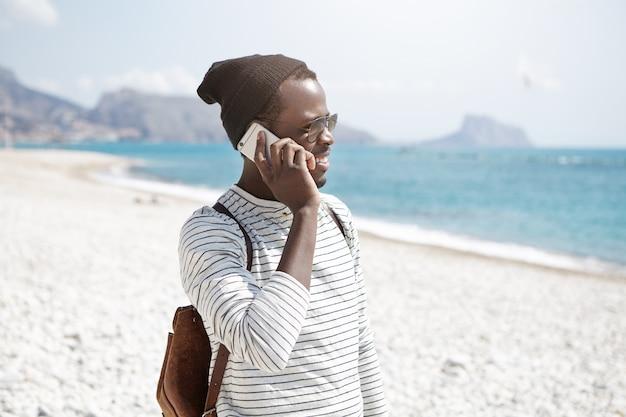 Chiuda sul ritratto all'aperto del viaggiatore con zaino e sacco a pelo nero in cappello che sta sulla spiaggia e che parla dal telefono