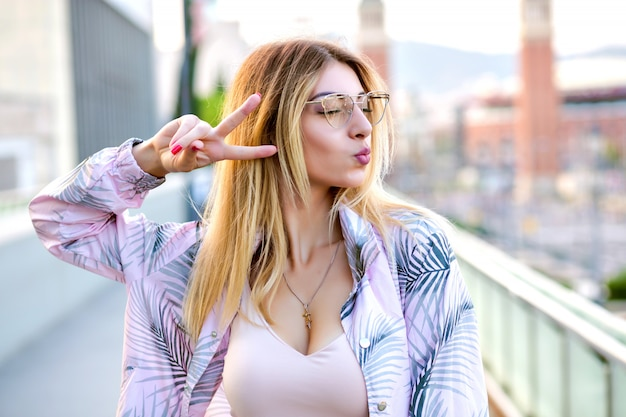 Close up outdoor portrait of blissful blonde woman, posing on the street, sending kiss and showing peace gesture, spring time, trendy clothes, soft toned colors.