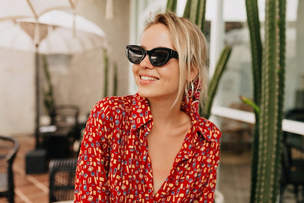 Chiuda sul ritratto all'aperto di donna graziosa amabile in occhiali da sole per godersi la vita e divertirsi