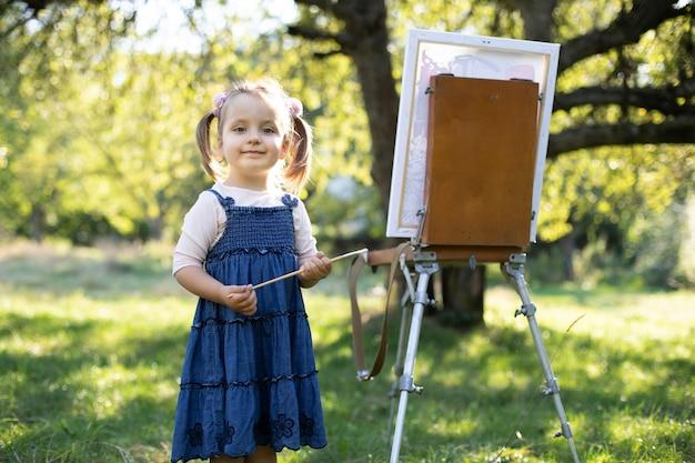 Закройте открытый портрет очаровательной маленькой девочки в джинсовом платье, позирующей с кистью в руках, стоя возле мольберта с холстом и рисующей картину в зеленом летнем парке.