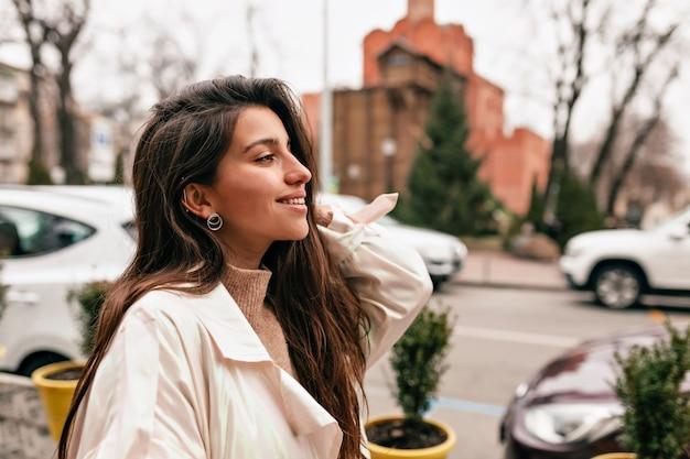 봄 날에 도시를 걷는 흰색 코트를 입고 검은 머리를 가진 매력적인 세련된 유럽 여자의 야외 초상화를 닫습니다