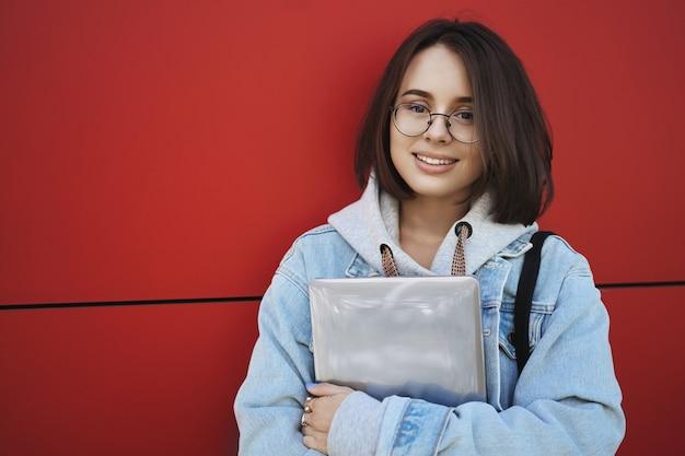 Крупным планом открытый портрет европейской студентки в очках, привлекательная девушка, стоящая возле красной стены, держа в руках ноутбук, улыбающаяся камера с веселым расслабленным выражением лица.