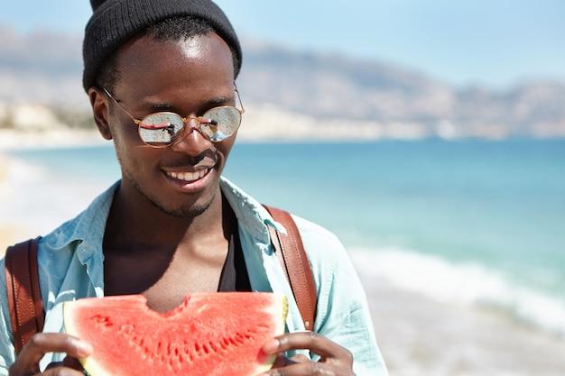 トレンディな色合いでハンサムな屈託のない笑顔のアフリカ系アメリカ人男性旅行者の屋外のポートレートを閉じて、海沿いを歩いて、新鮮な熟したスイカを食べる帽子