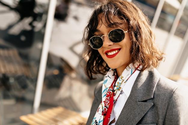 日光の下で街の波状の短い髪型で愛らしい笑顔の女の子の屋外の肖像画をクローズアップ