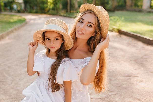 公園でお母さんとポーズをとっている間、目をそらしているかなり暗い目の女の子のクローズアップ屋外の肖像画。道路上の娘の近くに立って、髪で遊んでいる流行の麦わら帽子を持つ魅力的な長髪の女性。