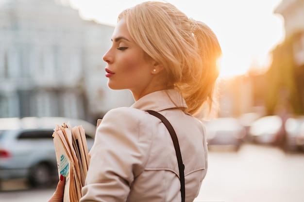 Крупным планом портрет романтической светловолосой девушки, держащей газету и позирующей с закрытыми глазами рано вечером