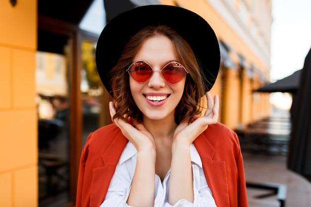かわいいオレンジ色のサングラス、ジャケット、黒い帽子で笑顔のヨーロッパの女の子の屋外のポートレートを閉じます。秋のファッション。